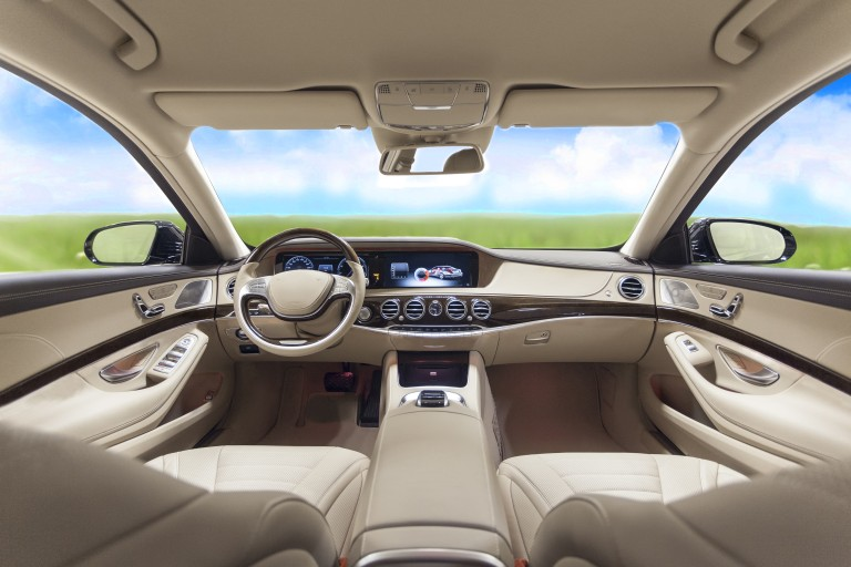 Beige colored interior of an upper class car viewing through the wind shield onto a green meadow and a blue sky