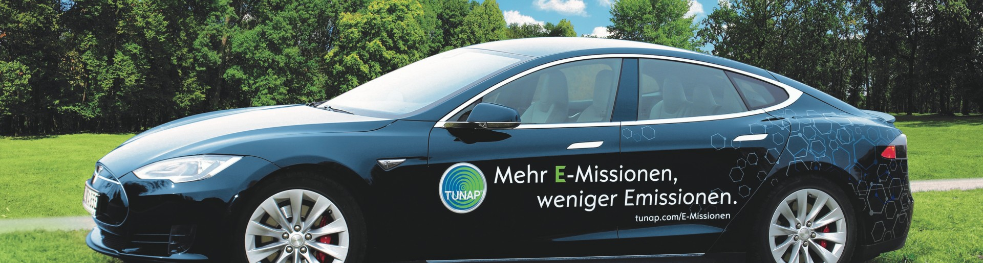 Side view of a dark blue sports car with white lettering and a TUNAP logo on a green meadow