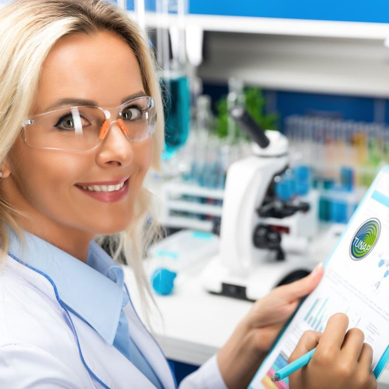 Smiling laboratory chemist with a writing pad and a microscope in the background